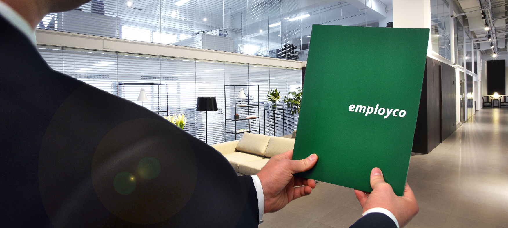 Shoulder shot of man in a suit holding out Employco folder.