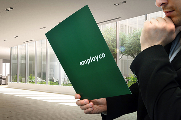 Man in suit holding in one hand Employco booklet and his chin in thought with the other hand.