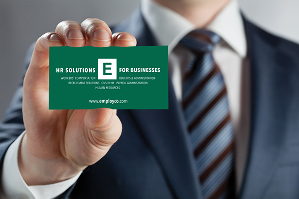 Man in suit holding Employco USA business card.